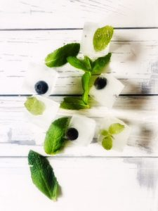 ice cubes with mint leaves and blueberries