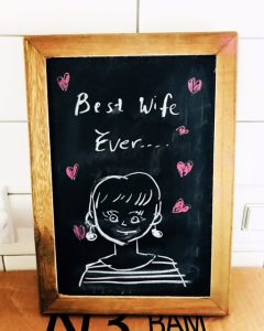 """best wife ever"" writen on a black board, along with a cartoon image of the author."