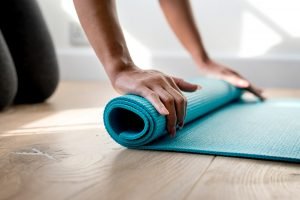 close up to hands rolling a yoga mat.