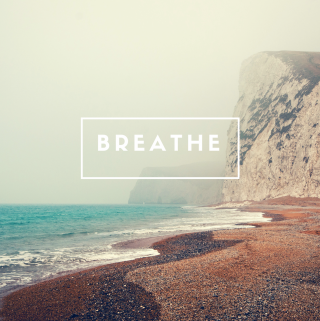 "a sign ""breathe"" embedded on the image on a beach"
