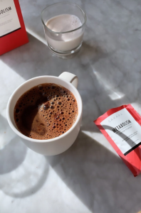 """A cup of cacao drink, next to a pack of """"metabolism super powder"""""""