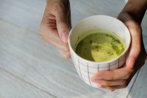 a woman holding a matcha cup