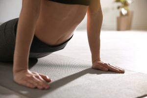 Woman doing yoga (cobra asana), close up.