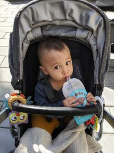 baby in a stroller, eating from a food pouch which he is holding.