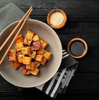 crispy tofu in a bowl with chopsticks. two small bowls (for sesame seeds and sauce) on the side.