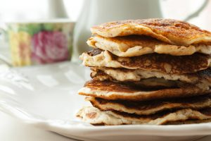 Low Carb Keto Diet Pancakes from almond coconut flour stack on white plate and cup of cocoa