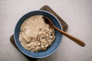 Flaxseed porridge with almonds and coconut milk in a blue bowl, wooden spoon on white marble table