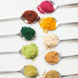 colourful superfood powders in spoons, placed on a flat surface
