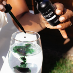 a woman dropping sakara life detox drops in a glass of water