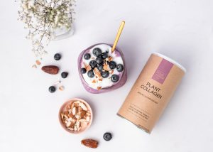 """""""plant collagen"""" superfoods container horizontally placed next to blueberry oats and nuts, on a flat surface."""