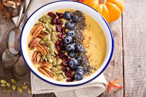 Pumpkin smoothie bowl with chia seeds, pecans, cranberries and blueberries